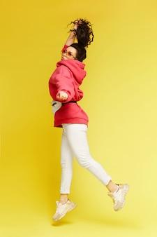 Jovem modelo mulher com cabelos cacheados e moletom puxando os cabelos para cima e pulando no fundo amarelo, isolado Foto Premium