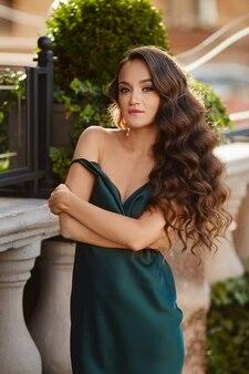 Jovem modelo mulher com corpo esguio em um vestido da moda posando ao ar livre num dia de verão