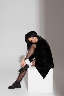 Jovem modelo mulher com corpo esguio perfeito em um vestido preto curto e um chapéu preto elegante posando sobre fundo branco