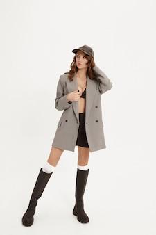 Jovem modelo mulher com corpo perfeito em uma jaqueta da moda e botas isoladas no fundo branco estúdio de moda tiro