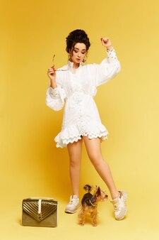 Jovem modelo mulher em óculos de sol da moda e vestido branco, posando com bolsa de ouro e yorkshire terri ...