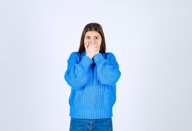 Jovem modelo na boca de coning de suéter azul com uma mão em branco-cinza.