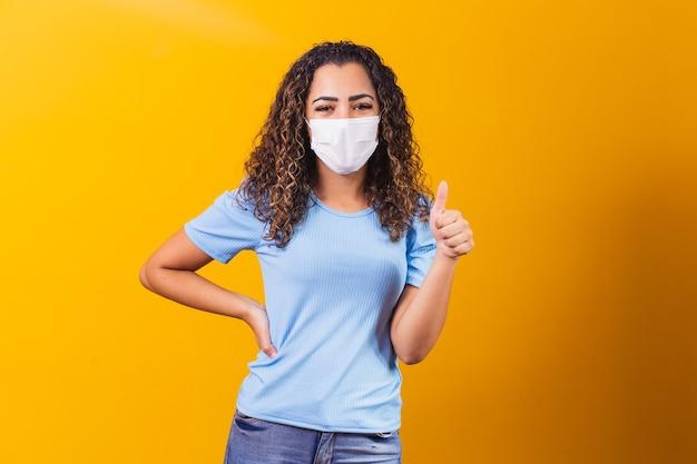 Jovem modelo negra usando máscara protetora com o polegar para cima