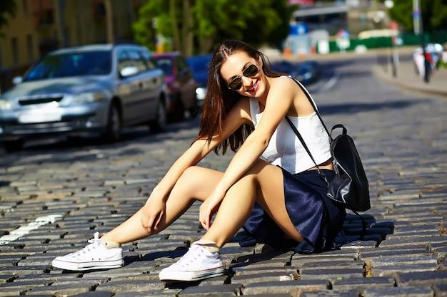 Jovem modelo no verão, sentado na rua