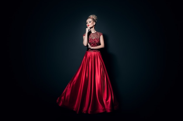 Jovem modelo posando isolada em um fundo preto com um vestido vermelho