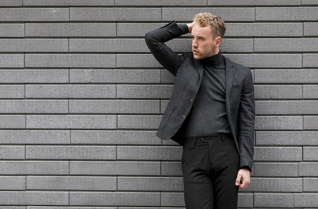Jovem modelo posando perto de uma parede cinza