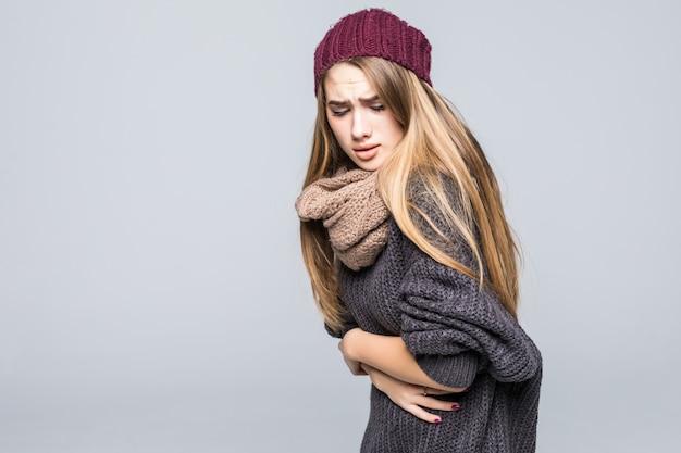 Jovem modelo vestida com moda tem dor de cabeça e estômago em cinza