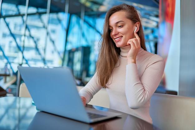 Jovem moderno casual feliz alegre mulher inteligente usando fones de ouvido sem fio usando laptop para assistir a vídeos e trabalhar remotamente online enquanto está sentado e descansando em um café