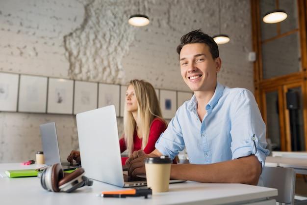 Jovem moderno e mulher trabalhando em um laptop em uma sala de escritório em parceria com espaço aberto