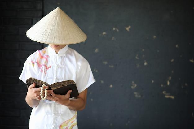 Jovem monge asiático com chapéu no fundo da parede preta