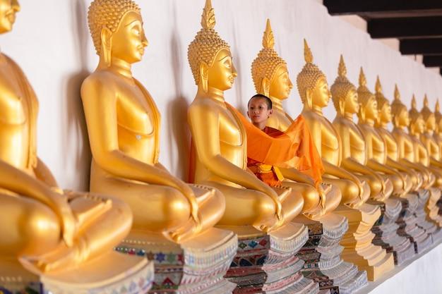 Jovem monge novato asiático cobrindo a estátua de buda de pano no templo wat phutthai sawan, em ayutthaya, tailândia