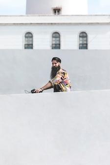 Jovem, montando, a, bicicleta, frente, parede
