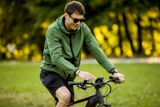 Jovem, montando ebike na natureza