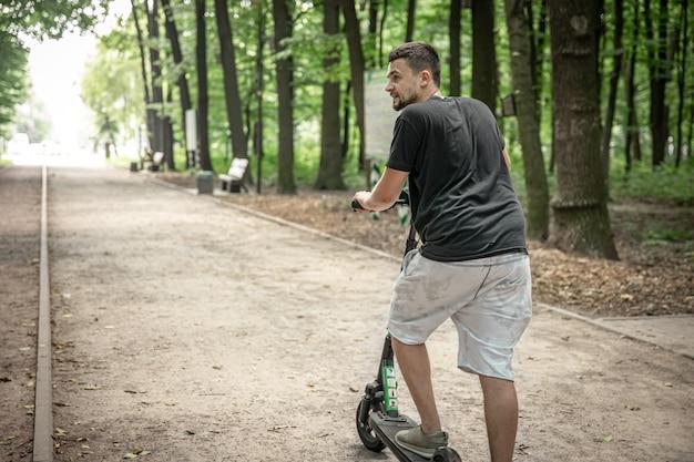 Jovem, montando uma scooter elétrica, conceito de transporte ecológico.