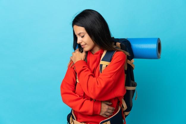 Jovem montanhista com mochila e dor no ombro por ter feito esforço