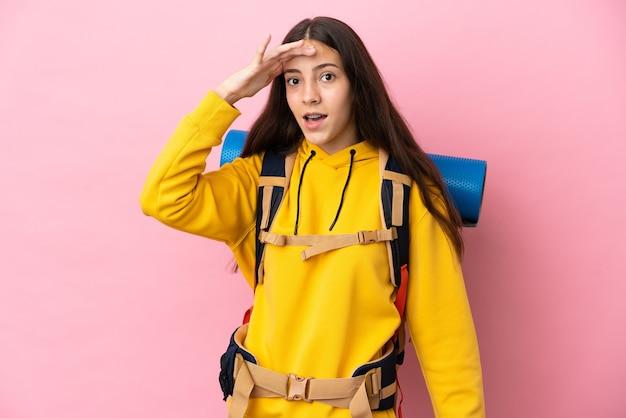 Jovem montanhista com uma grande mochila isolada em um fundo rosa fazendo gesto surpresa enquanto olha para o lado