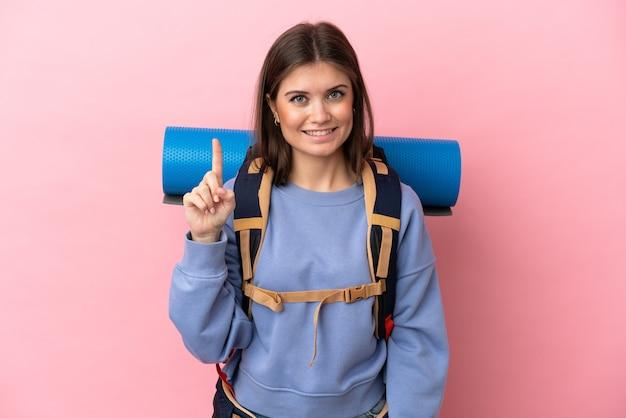 Jovem montanhista com uma grande mochila isolada mostrando e levantando o dedo em sinal dos melhores