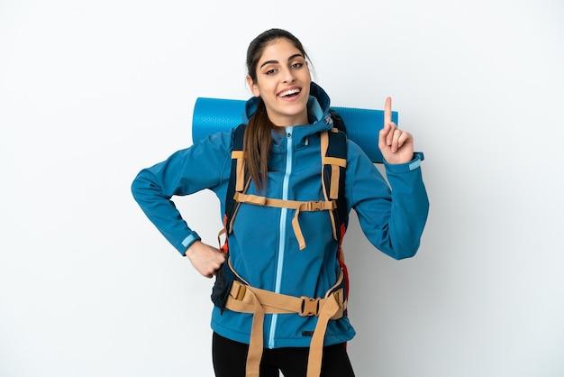 Jovem montanhista com uma grande mochila sobre fundo isolado, mostrando e levantando um dedo em sinal dos melhores
