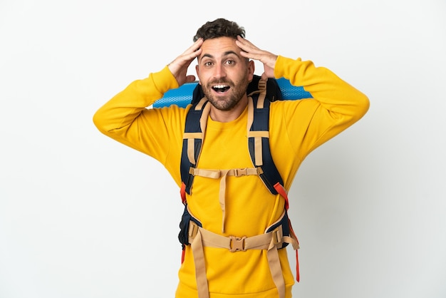 Jovem montanhista com uma grande mochila sobre uma parede isolada com expressão de surpresa