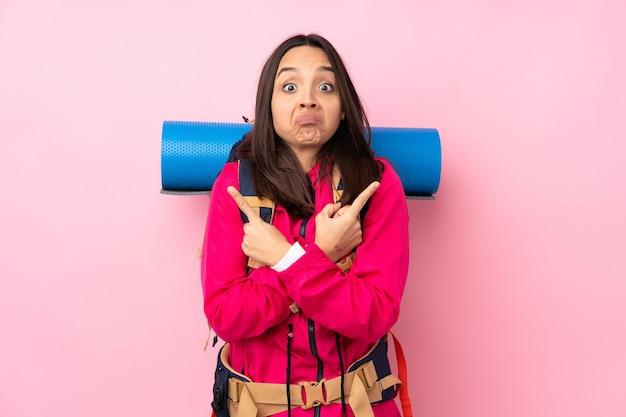 Jovem montanhista com uma grande mochila sobre uma parede rosa isolada apontando para as laterais com dúvidas