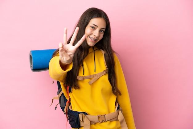 Jovem montanhista com uma mochila grande isolada em um fundo rosa feliz e contando três com os dedos