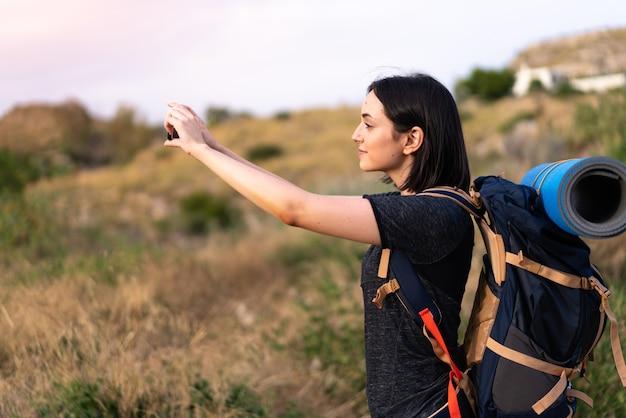 Jovem montanhista tirando uma selfie com o celular com uma mochila grande ao ar livre