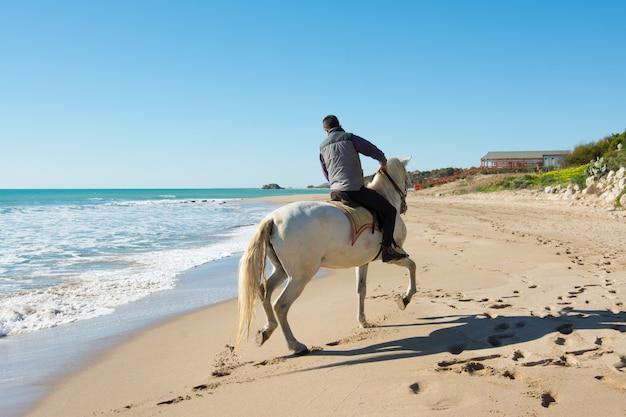 Jovem montar um cavalo branco na praia