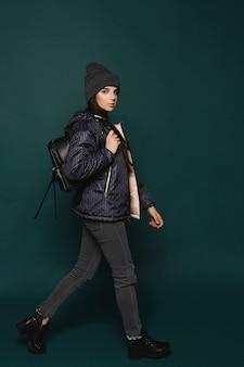 Jovem morena adolescente, de casaco e chapéu com uma bolsa, caminhando sobre um fundo verde escuro, isolada