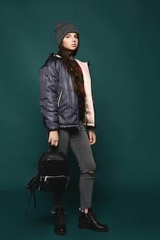 Jovem morena adolescente, de jaqueta e chapéu com uma bolsa, em pé sobre um fundo verde escuro, isolado