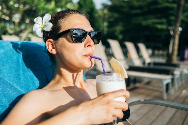 Jovem morena alegre bronzear perto da piscina do hotel