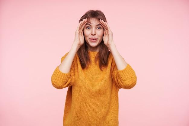 Jovem morena alegre de olhos azuis com penteado casual levando as mãos ao rosto e olhando com alegria, vestida com um suéter de malha mostarda enquanto posava sobre uma parede rosa