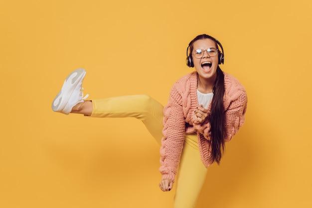 Jovem morena alegre em copos dançando, ouvindo música em fones de ouvido altos, levantando a perna vestida com calças amarelas, sapatos brancos, blusa rosa e fones de ouvido na cabeça