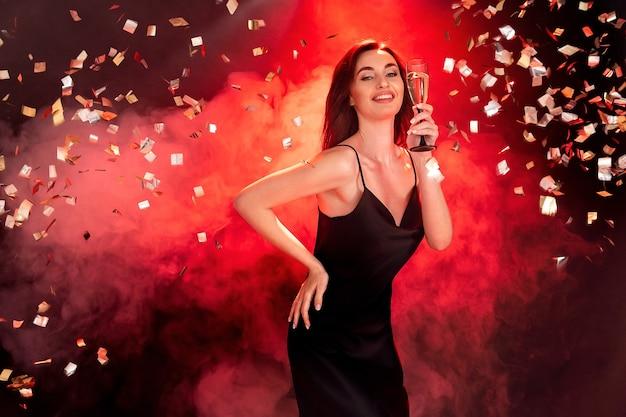 Jovem morena animada de vestido preto segurando uma taça de champanhe, hora da festa, conceito de férias