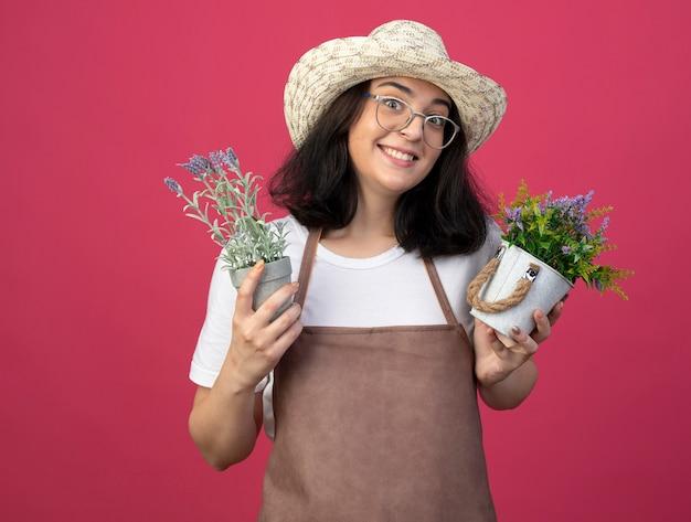 Jovem morena animada, jardineira feminina, de óculos ópticos e uniforme, usando um chapéu de jardinagem, segura vasos de flores isolados na parede rosa com espaço de cópia