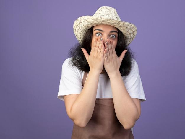 Jovem morena animada, jardineira feminina de uniforme, usando chapéu de jardinagem, coloca as mãos na boca isolada na parede roxa