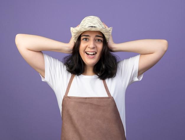 Jovem morena animada, jardineira feminina de uniforme, usando chapéu de jardinagem, coloca as mãos na cabeça isolada na parede roxa