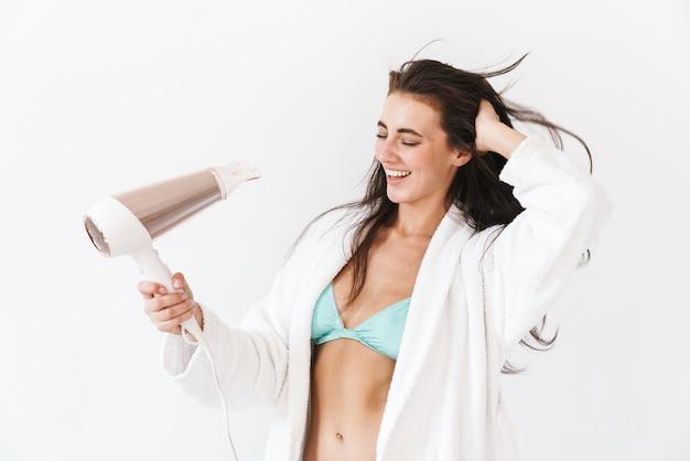 Jovem morena animada usando biquíni sob o roupão de banho em pé, isolada no branco, secando o cabelo com um secador de cabelo