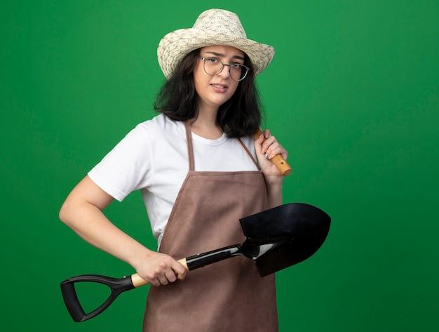 Jovem morena ansiosa, jardineira feminina de óculos óticos e uniforme, usando chapéu de jardinagem, segura o ancinho e a pá isolados na parede verde