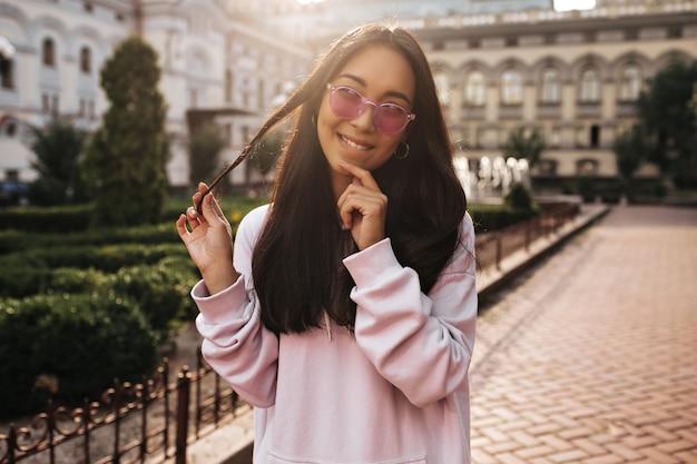 Jovem morena asiática com óculos de sol rosa e um capuz estiloso parece pensativa, brinca com o cabelo e faz poses do lado de fora