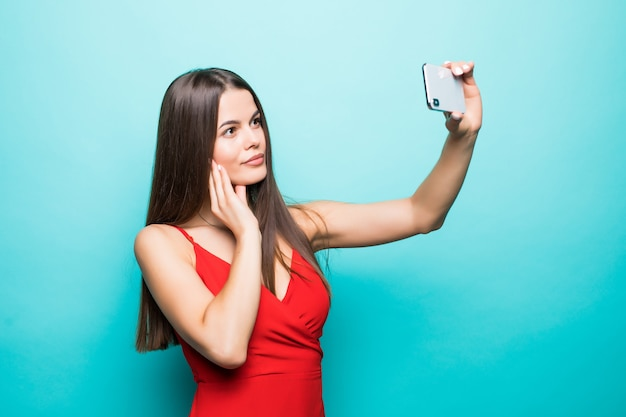 Jovem morena atraente alegre está sorrindo na parede azul. ela está tirando uma selfie com o telefone, usando uma roupa casual de verão e um chapéu
