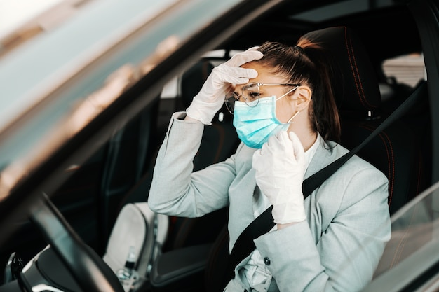Jovem morena atraente com máscara facial, com luvas de borracha segurando a cabeça porque ela está tendo dor de cabeça enquanto está sentada em seu carro durante o surto do vírus corona.