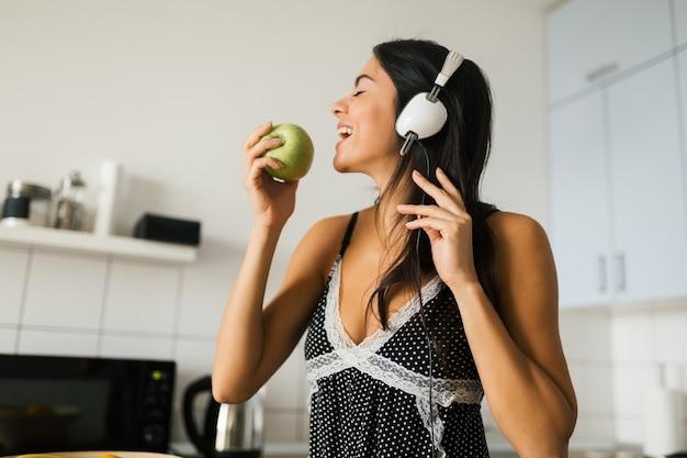 Jovem morena atraente cozinhando na cozinha pela manhã, comendo maçã verde, sorrindo, humor feliz, dona de casa positiva, estilo de vida saudável, ouvindo música em fones de ouvido, mordendo