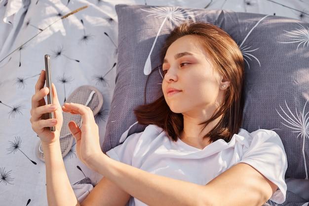 Jovem morena atraente deitada em um travesseiro macio na cama ao ar livre e usando o telefone celular