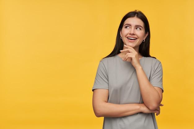Jovem morena atraente e alegre em uma camiseta cinza com as mãos cruzadas, sorrindo e olhando para o lado na copyspace sobre a parede amarela