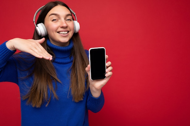 Jovem morena atraente, feliz e sorridente, vestindo uma blusa azul isolada sobre fundo vermelho