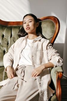 Jovem morena atraente mulher asiática em jaqueta estilosa, calça bege e camiseta branca olha para a câmera e se senta no sofá de veludo