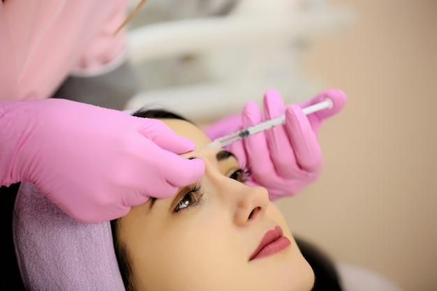 Jovem morena bonita recebe rejuvenescimento injeções faciais.
