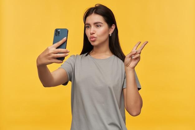 Jovem morena brincalhona encantadora com camiseta cinza mostrando o símbolo da paz, mandando um beijo, fazendo cara de pato e tirando selfie usando smartphone sobre a parede amarela