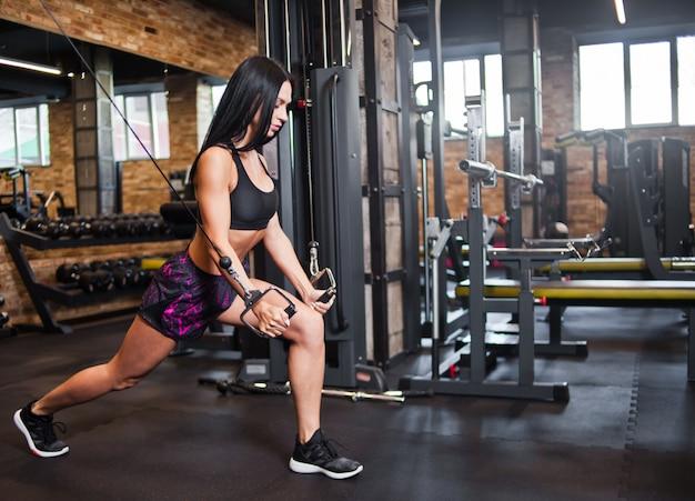 Jovem morena cabe mulher executar exercício com máquina de exercício no ginásio