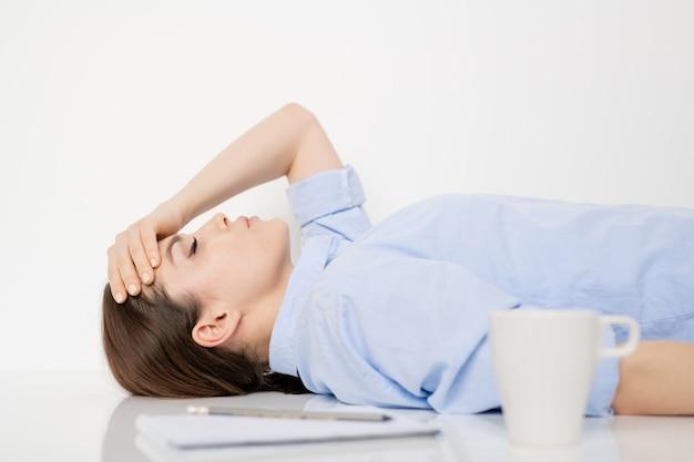 Jovem morena cansada, estressada ou com problemas, mantendo a mão na testa enquanto está deitada na mesa perto da parede branca